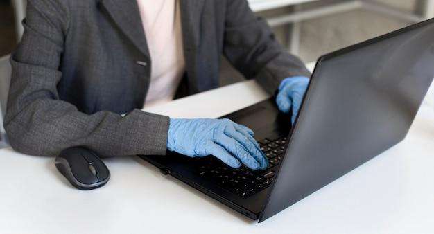 Close-up vrouw die werkt op kantoor met chirurgische handschoenen Gratis Foto