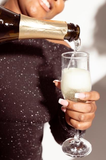 Close-up vrouw een glas champagne gieten Gratis Foto