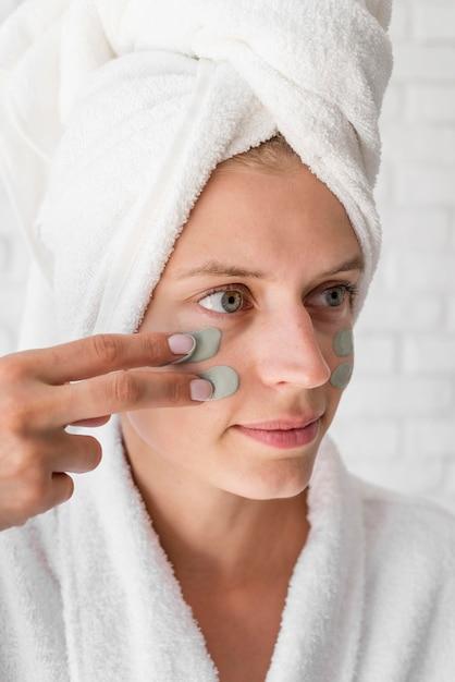 Close-up vrouw gezicht remedie toe te passen Gratis Foto