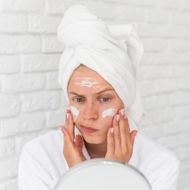 Close-up vrouw gezichtsmasker zetten Gratis Foto