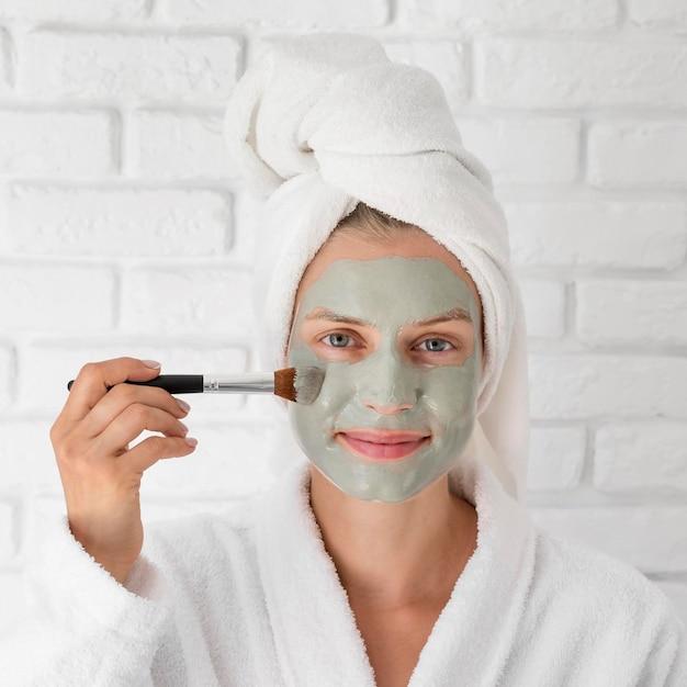 Close-up vrouw groen gezichtsmasker zetten Gratis Foto