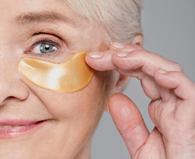 Close-up vrouw met behulp van ooglapje Premium Foto
