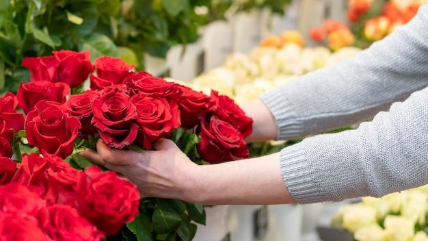 Close-up vrouw met collectie van rode rozen Gratis Foto