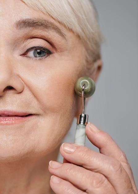 Close-up vrouw met gezichtsroller Gratis Foto