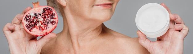 Close-up vrouw met granaatappel en room Gratis Foto