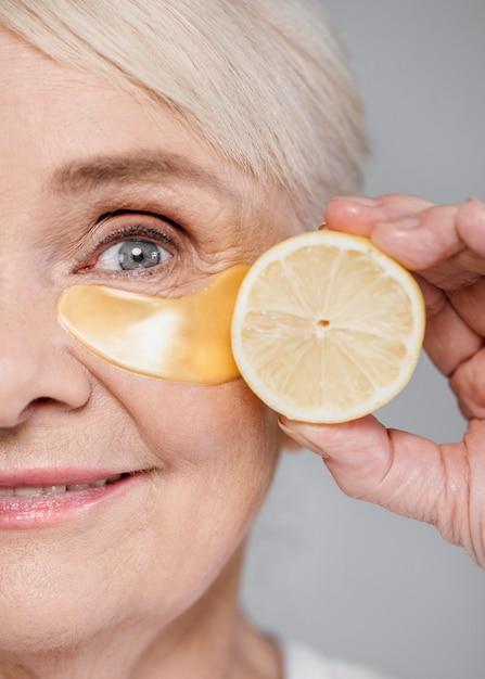 Close-up vrouw met oog patch en schijfje citroen Premium Foto