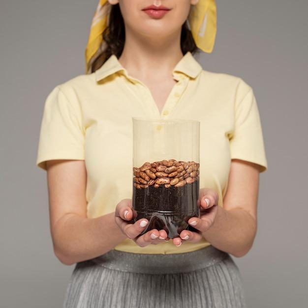 Close-up vrouw met plasic fles met geplante bonen Gratis Foto