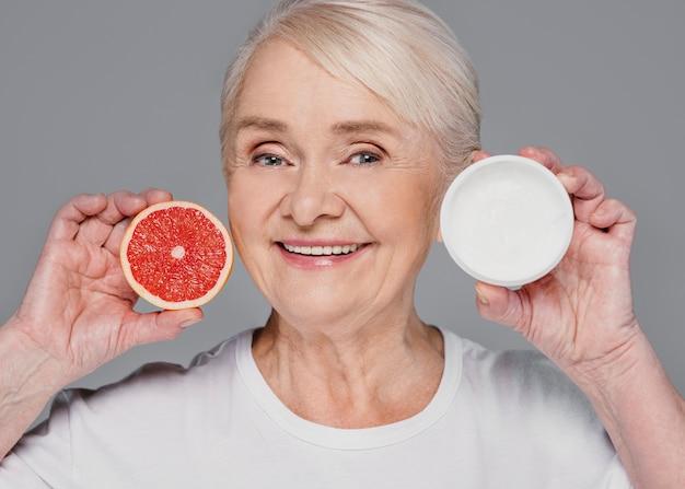 Close-up vrouw met rode sinaasappel en room Gratis Foto