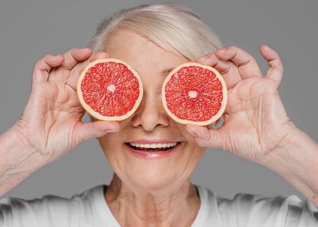 Close-up vrouw met rode stukjes sinaasappel Gratis Foto