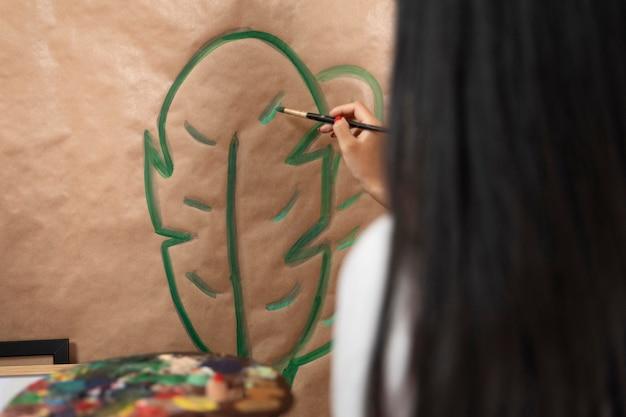 Close-up vrouw schilderij blad Gratis Foto