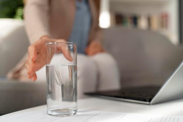 Close-up vrouw therapeut bereiken voor glas water Premium Foto