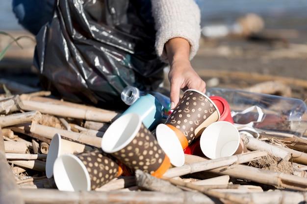Close-up vrouwelijke plukken afval van zee Gratis Foto