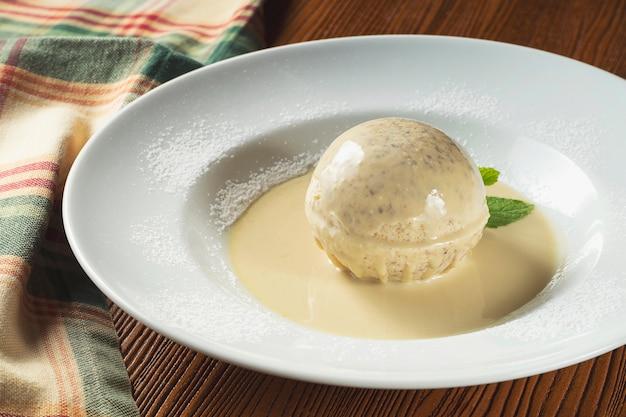 Close-up wit italiaans ijs in witte chocolade bal met gesmolten witte chocolade in plaat met munt. Premium Foto