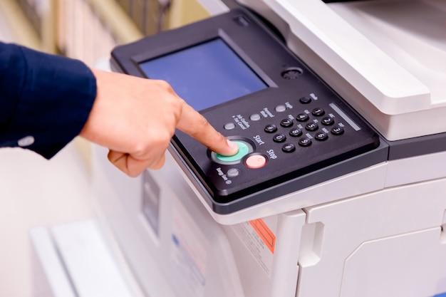 Close-up zakelijke man hand drukknop op het paneel van de printer, printer scanner laser kantoor kopie machine levert start concept. Premium Foto