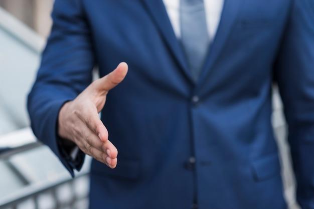 Close-up zaken man bereid om de hand te schudden Gratis Foto