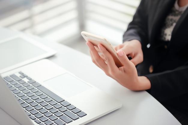 Close-up zakenvrouw handen met behulp van slimme telefoon en touchscreen Premium Foto