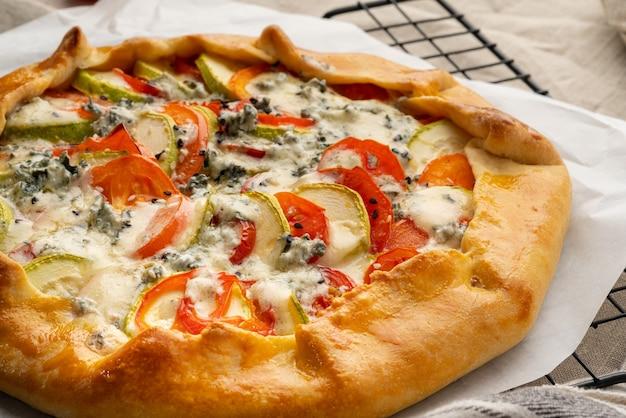 Close-up zelfgemaakte hartige galette met groenten, tarwe taart met tomaten, courgette, blauwe kaas gorgonzola. rustieke korstcrostata op donker linnen textieltafelkleed. Premium Foto