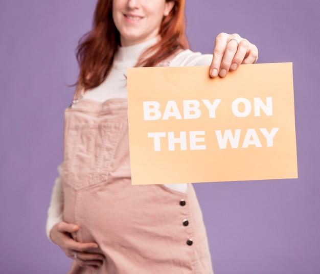 Close-up zwangere vrouw met papier met baby onderweg bericht Gratis Foto