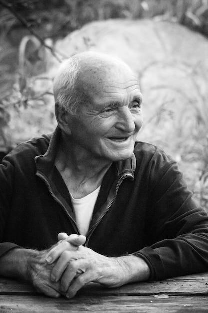 Close-up zwart wit portret van een zeer oude man met gekruiste armen, zittend aan een tafel Premium Foto