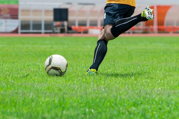 Close-upbeeld, de voetballers staan op het punt om de bal te schoppen die op het gazon is geplaatst. Premium Foto