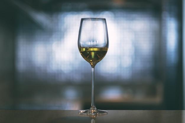 Close-upbeeld van champagne in een wijnglas met vage lichte achtergrond Premium Foto