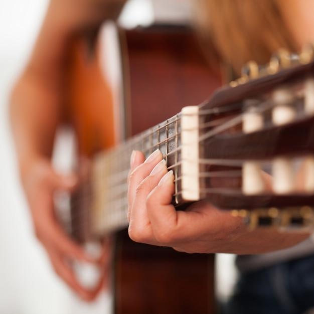 Close-upbeeld van gitaar in vrouwenhanden Gratis Foto