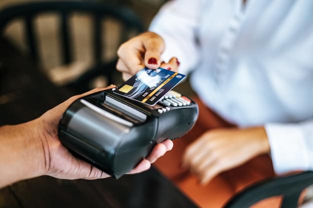 Close-upbeeld van vrouw die met creditcard in koffie betalen Gratis Foto