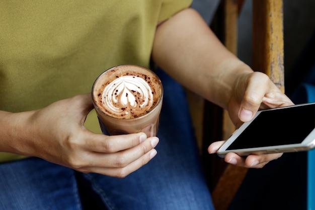 Close-upbeeld van vrouw of mannelijke handen die smartphone gebruiken bij koffie terwijl het drinken van koffie Premium Foto
