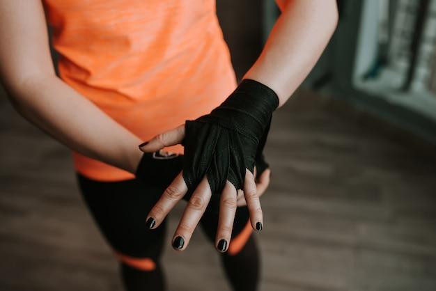 Close-upbeeld van vrouwelijke hand met zwarte riem. voorbereiding op het boksen. Premium Foto