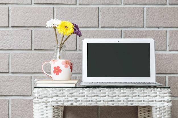 Close-upcomputer op houten weefsellijst en de bruine achtergrond van de bakstenen muurtextuur Premium Foto