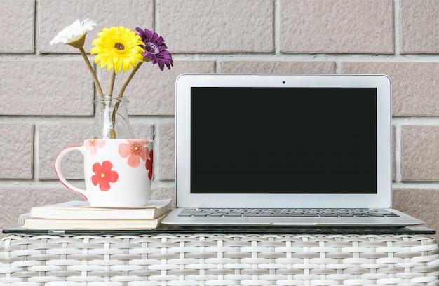 Close-upcomputer op vage houten weefsellijst en de bruine achtergrond van de bakstenen muurtextuur Premium Foto
