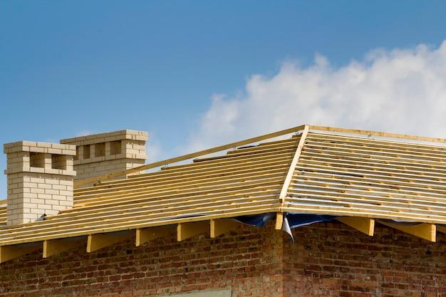 Close-updetail van houten dak van nieuw baksteenhuis met twee witte schoorstenen in aanbouw. houtkader van natuurlijke materialen tegen heldere hemel. professioneel bouw- en wederopbouwconcept. Premium Foto