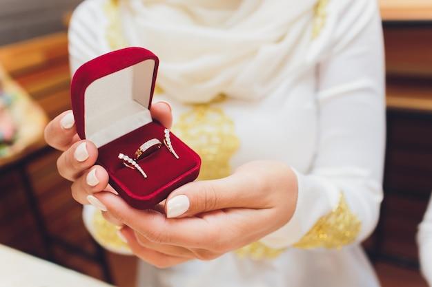 Close-upfoto van bruid en bruidegomholdingsdoos met gouden ringen. Premium Foto