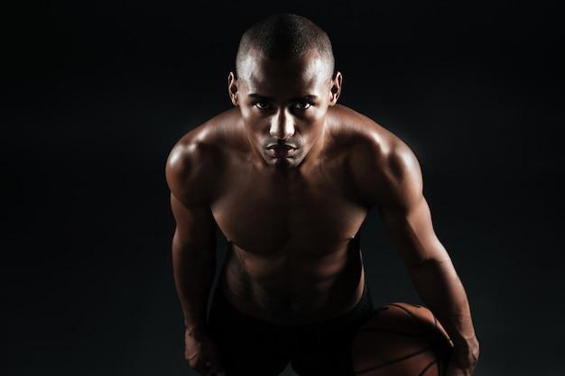 Close-upfoto van de bal van de de spelerholding van het afro amerikaanse basketbal Gratis Foto