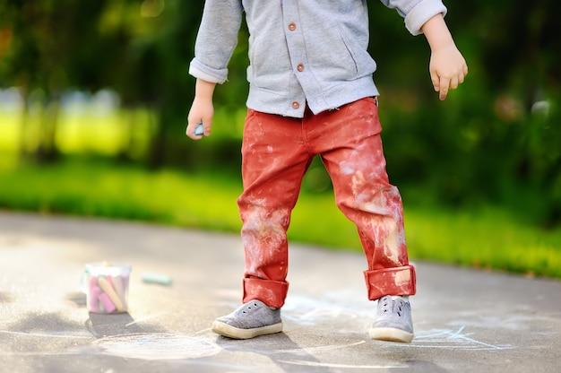 Close-upfoto van de kleine tekening van de jong geitjejongen met gekleurd krijt op asfalt. Premium Foto