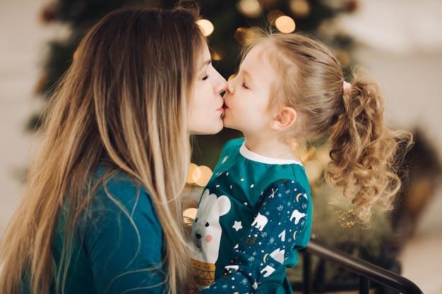 Close-upfoto van een donkerbruine dame die een klein meisje kust met de kerstboom. concept vakantie Premium Foto