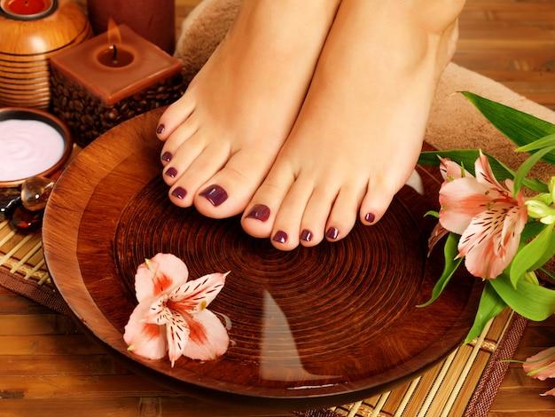 Close-upfoto van een vrouwelijke voeten bij kuuroordsalon op pedicureprocedure. benen zorg concept Gratis Foto