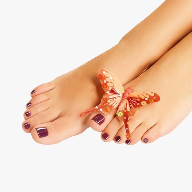 Close-upfoto van een vrouwelijke voeten met mooie pedicure na kuuroordprocedure op wit Gratis Foto