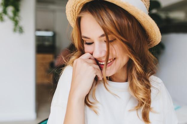 Close-upfoto van geweldig gelukkig meisje met bleke huid verlegen lachen en gezicht bedekken met hand Gratis Foto