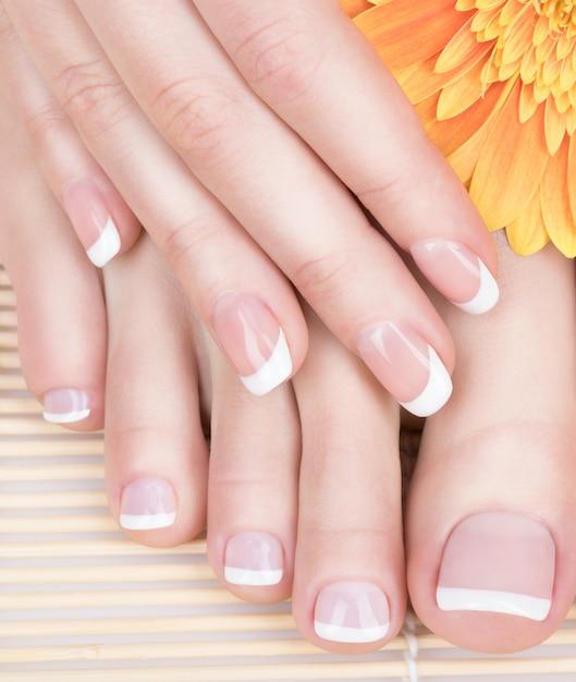 Close-upfoto van vrouwelijke voeten bij kuuroordsalon op pedicure en manicureprocedure - softfocusbeeld Gratis Foto