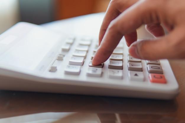 Close-uphand die calculator gebruiken die als zaken en financieel concept gebruiken Premium Foto