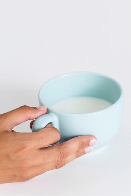 Close-uphand die ceramische kop met melk houden Gratis Foto