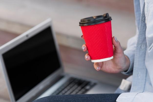 Close-uphand die een kop van koffie houden Gratis Foto