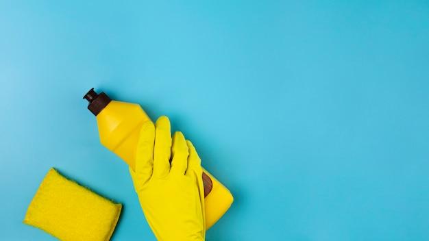 Close-uphand met gele handschoen op blauwe achtergrond Gratis Foto