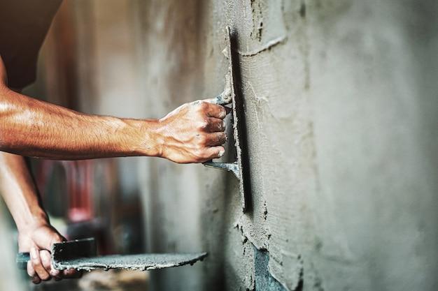 Close-uphand van arbeider het pleisteren cement bij muur voor de bouw van huis Premium Foto