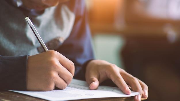 Close-uphand van het schrijven van examen met studenten op cursus. Premium Foto