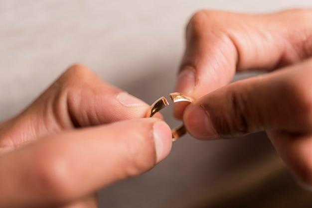 Close-uphanden die gebroken ring houden Gratis Foto