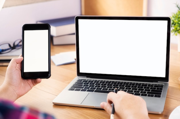 Close-uphanden die smartphone gebruiken bij het bureau. Premium Foto