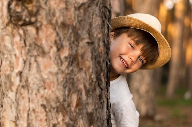Close-upjong geitje die achter boom verbergen Gratis Foto