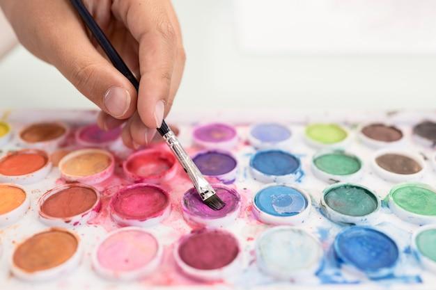 Close-upjongen die aquarelle thuis gebruiken Gratis Foto